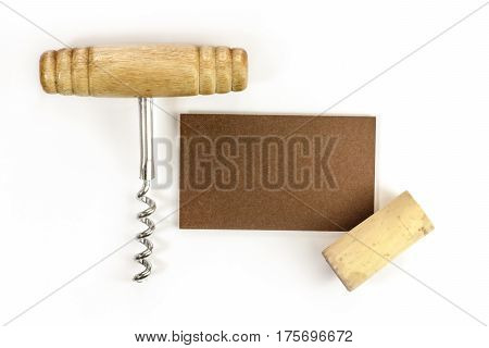 A photo of a bronze business card with a cork and a corkscrew, shot from above on a white background. Design template for a wine list or tasting invitation