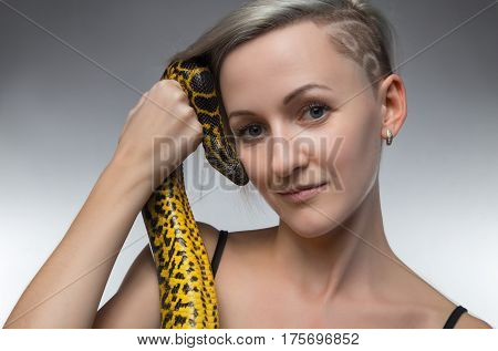 Smiling woman holding yellow snake on gray background