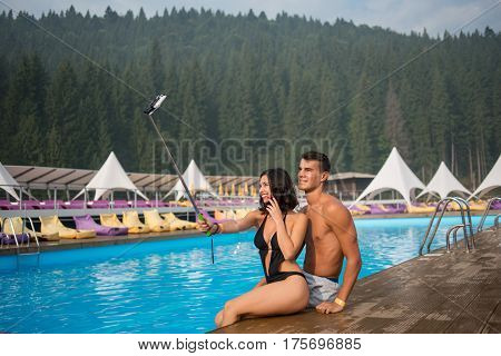 Two friends girl and guy sitting on the edge of swimming pool at the luxurious resort and making selfie photo on the phone with selfie stick. Mighty forests on the background