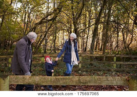Multi Generation Family Enjoying Walk In Fall Landscape