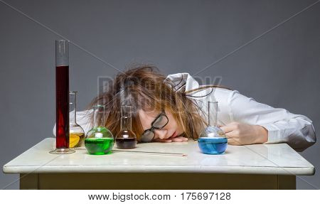 Sleeping scientist with glass flask on gray background