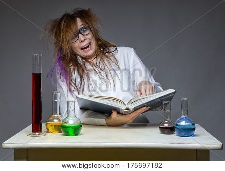 Reading laughing scientist with glass flask on gray background