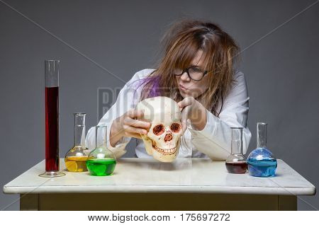 Exploring scientist with human skull on gray background