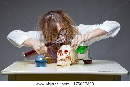 Mixing liquid professor with human skull on gray background
