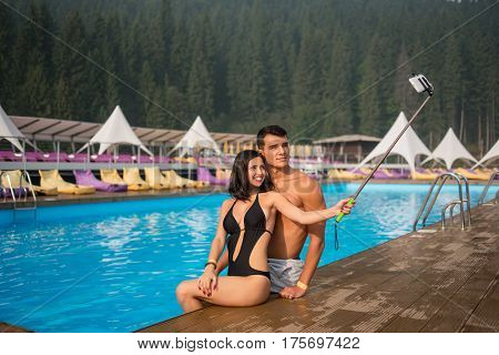 Happy Couple Girl And Guy Sitting On The Edge Of Swimming Pool At The Luxurious Resort And Taking Se