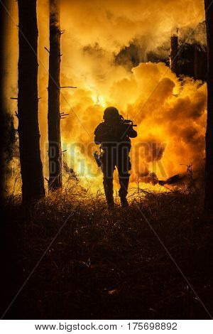 Backlit silhouette of special forces marine operator in forest on fire explosion background. Battle, bombs exploding, fighting no matter what