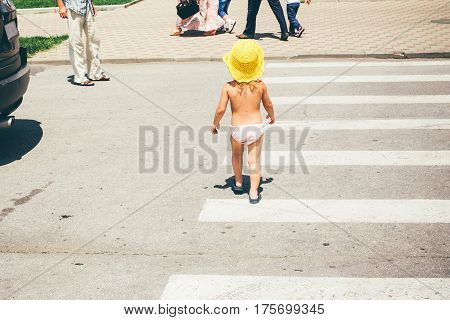 A Small Child Crosses The Street On A Pedestrian Crossing Strolling.