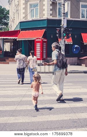A small child crosses the street on a pedestrian crossing strolling in the summer in clear weather. The concept of children and the safety of transportation in the city.