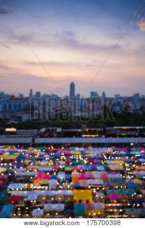 Blurred bokeh light nigth market aerial view with city downtown background