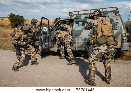 Squad of elite french paratroopers of 1st Marine Infantry Parachute Regiment RPIMA detaining terrorist in the car poster