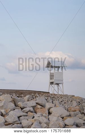 Lifeguard stand over rocky coastline with soft blue sky background