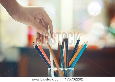 Human hand taking taking pencils. Horizontal photo