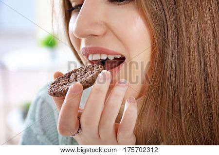 Young woman eating cookie, closeup