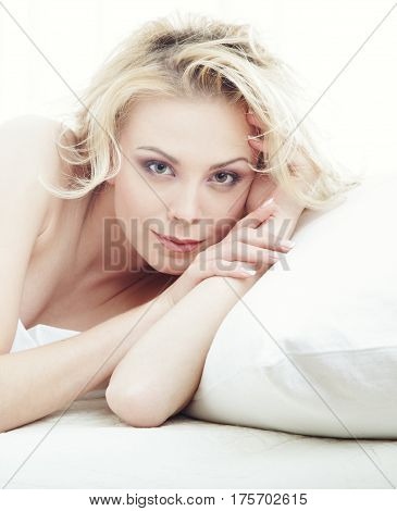 Portrait of the blond lady laying on a pillow