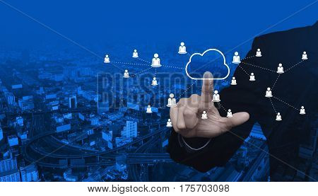 Businessman pressing cloud button with business network over modern city tower street and expressway Internet concept