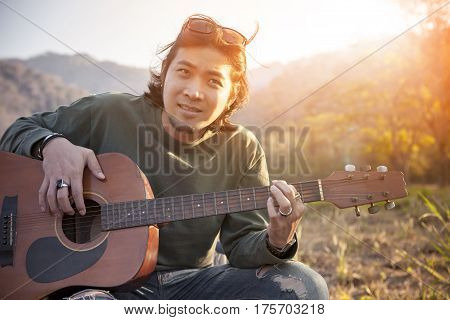 asian younger man relaxing outdoor with old guitar for people leisure vacation and traveling