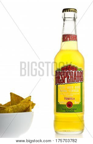 GRONINGEN, NETHERLANDS - MARCH 04, 2017: Bottle of Mexican Desperados beer with nachos isolated on a white background