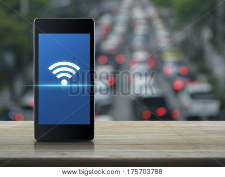 Wi-fi connection icon on modern smart phone screen on wooden table over blur of rush hour with cars and road Technology and internet concept