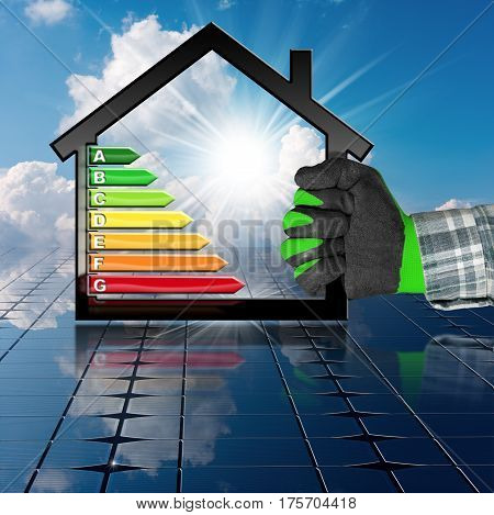 Hand with work glove holding a symbol in the shape of house with energy efficiency rating (3D illustration) on a solar panel and sky (photo)