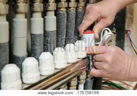 Installation of home heating. Men's hands attaches the servo valve drive underfloor heating.