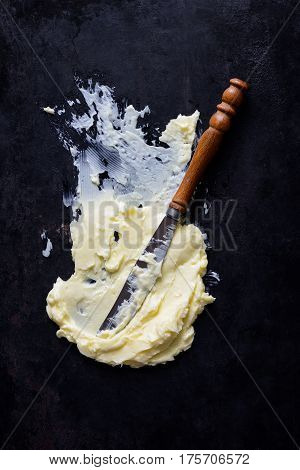 Butter or margarine spread on a dark rustic surface with a knife view from above