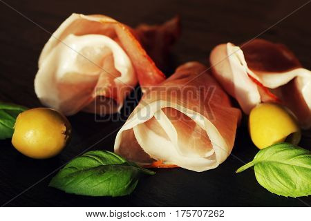 Curled Slices of Delicious Prosciutto with basil leaves and olives on granite board.