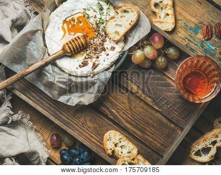 Homemade camembert cheese with honey and herbs in small pan, grapes, baguette slices, pecan nuts and glass of rose wine over rustic wooden background, top view, copy space