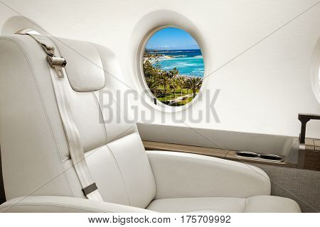 Aiircraft porthole with view of sea and beach resort, flight by business class