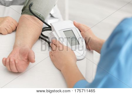 Doctor measuring pressure of elderly woman with digital sphygmomanometer while sitting at table