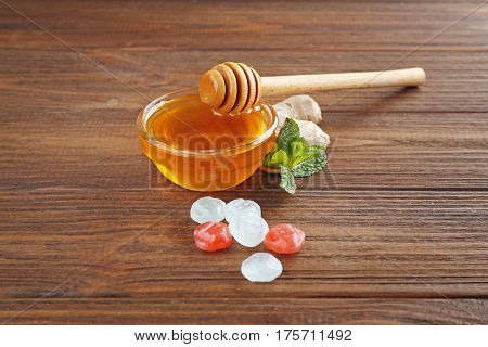 Cough drops with honey on wooden background