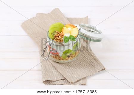 jar of muesli with yogurt and fresh fruit on beige place mat