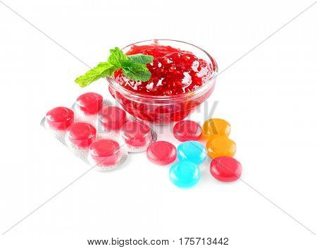 Different cough drops with jam on white background