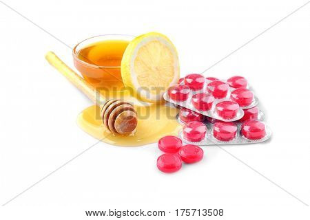 Cough drops with honey and lemon on white background