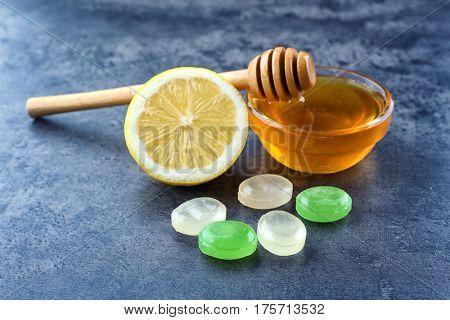 Cough drops with honey and lemon on color background