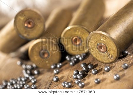 Closeup of shotgun shells and shot on wood background poster