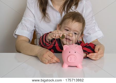 Little Girl Is Putting Coins In Piggy Money Bank.