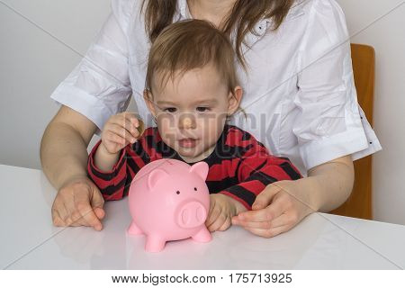 Little Girl Is Putting Coins In Piggy Money Bank And Collecting
