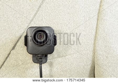 lens from the camcorder security police body camera with power cord in black color on a white suit jacket vertical image