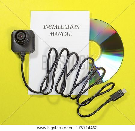 new video lens the camera body electrical cord instructions for use of the device in paper form and on CD-ROM on a yellow background