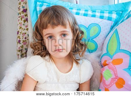 sad little girl with big gray eyes and angel wings