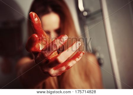 Woman with bloody hand in shower