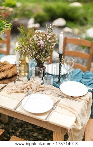 spring festive lunch an outdoors, wedding decor of a table, table layout, the fresh cut bread, bouquet of wild flowers.