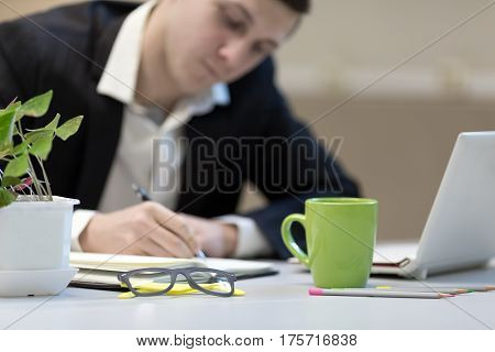 Businessman making Hand notes at cozy Office working Place with Flower Glasses green Coffee Mug and Computer