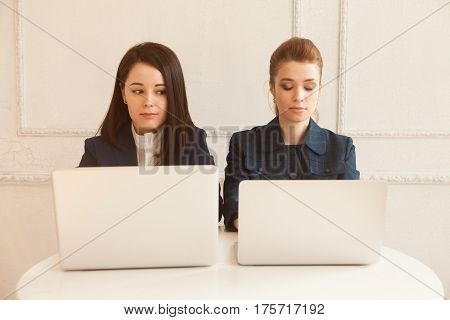 Front view of two businesswomen looking each other working with laptops at office