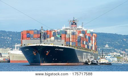 Oakland CA - March 07 2017: Cargo Ships are unable to maneuver sideways. Tugboats Z-FIVE and MICHELLE SLOAD turn cargo ship NYK ATHENA 180 degrees prior to docking at the Port of Oakland.