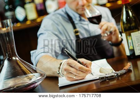 Male sommelier tasting red wine and making notes at bar counter. Bottle of wine nearby. Professional expert appreciates quality of alcoholic beverage, degustation process