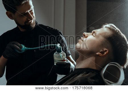 BARBERSHOP THEME. BEARDED BARBER IN BLACK RUBBER GLOVES  SPLASHES AFTER SHAVING LOTION FROM THE SPRAY BOTTLE ON CLIENT'S SKIN