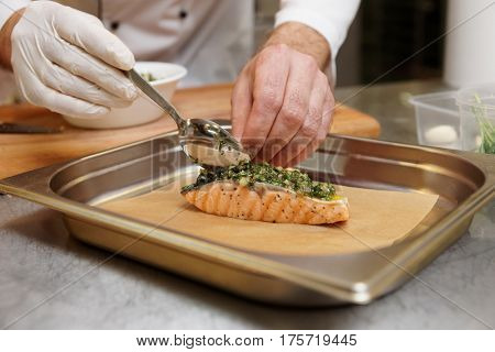 Chef is putting herbal sauce on grilled salmon steak to make a savory crust