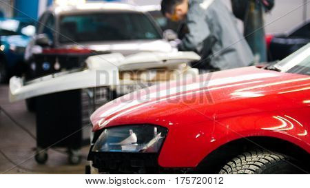 Defocused background - professional car service - man work tinsmith works with a hammer - repairing automobile, telephoto
