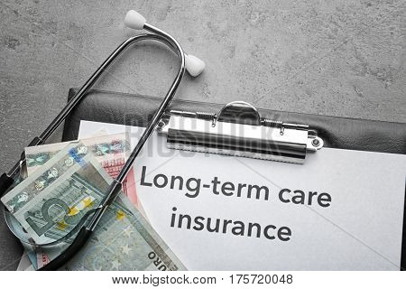 Text LONG-TERM CARE INSURANCE on clipboard with stethoscope and euros on grey textured background